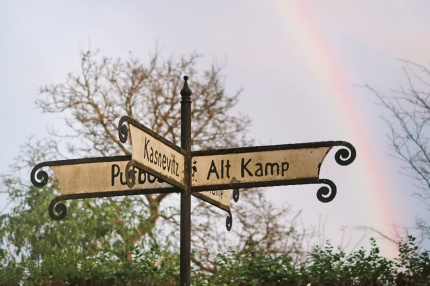 Historical Signposts with Rainbow - Photo by Sabine Eisenknappl