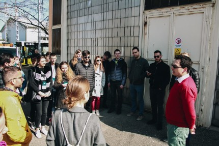 People standing in a circle outside an industrial building listening to man speaking to the whole group