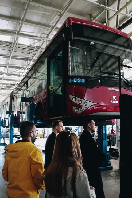 People looking at a trolleybus that is being suspended by a jack