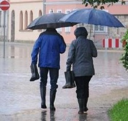Picture of two people using an umbrella together walking on the street